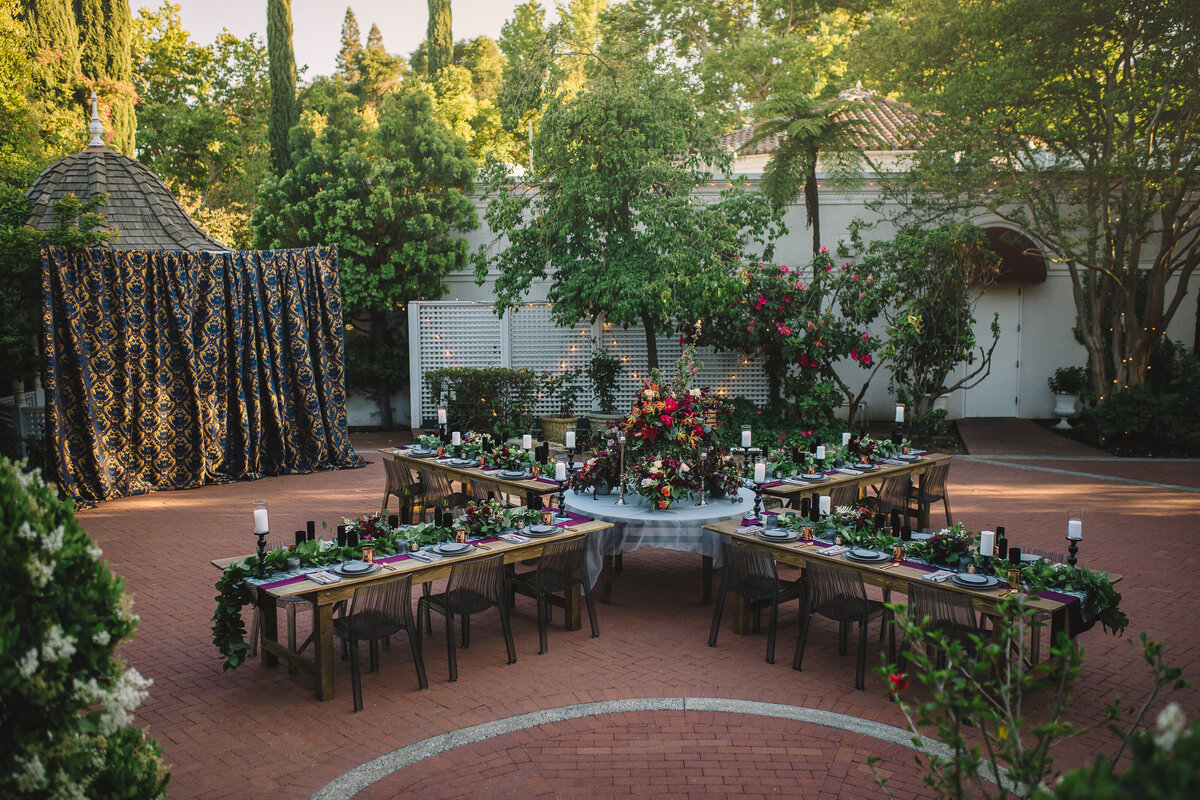 A uniquely designed floorplan, this outdoor bridal shower set up with farm house tables and moody florals is a great addition to the Gardens Courtyard.