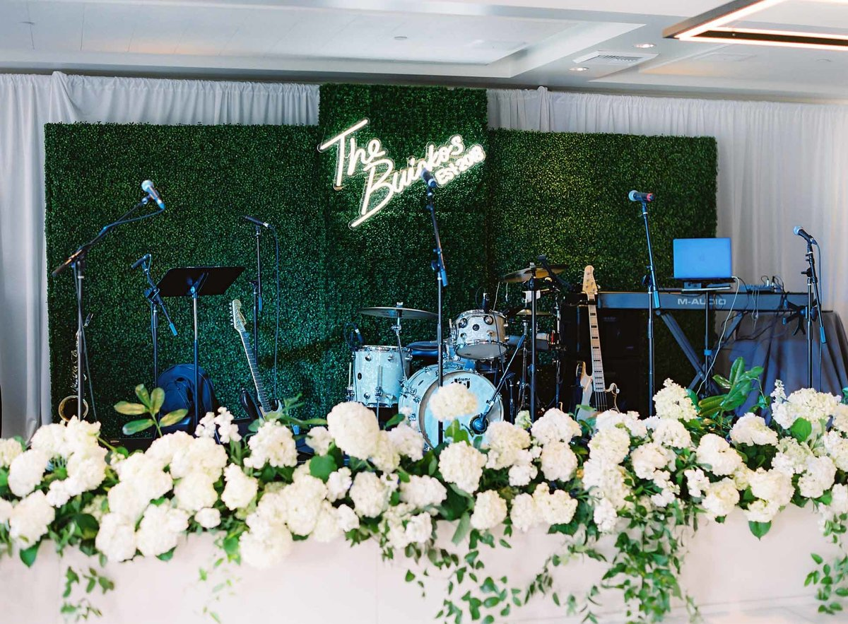 The couple created a custom neon sign to hang on our green hedge backdrop behind the live band, combined with the planters filled with hydrangea this is one of my favorite reception spaces.