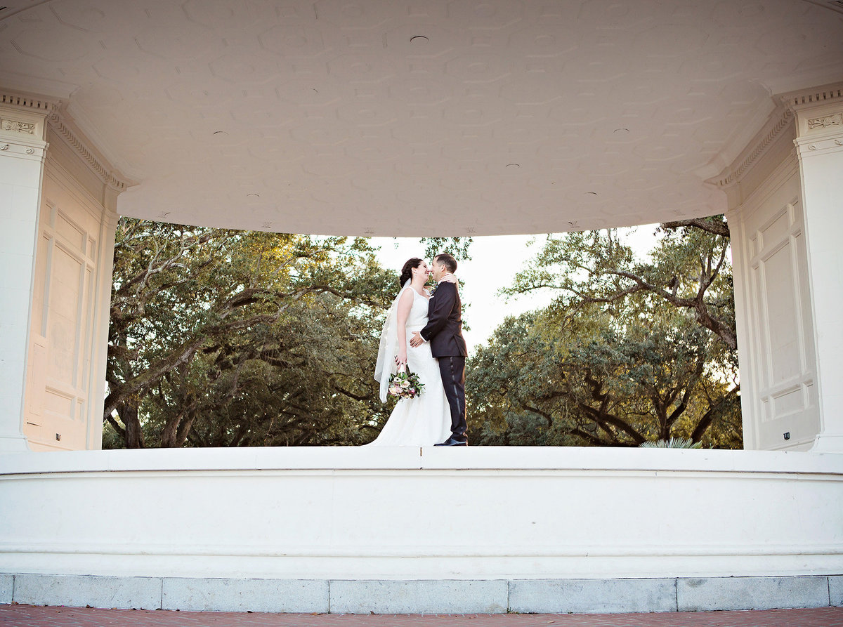 bride and groom kissing under The Newman Bandstand in Audubon Park