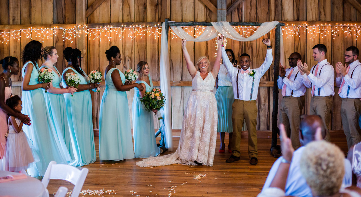 Bride and groom stand with their arms raised at the end of their Betsy's Barn wedding ceremony
