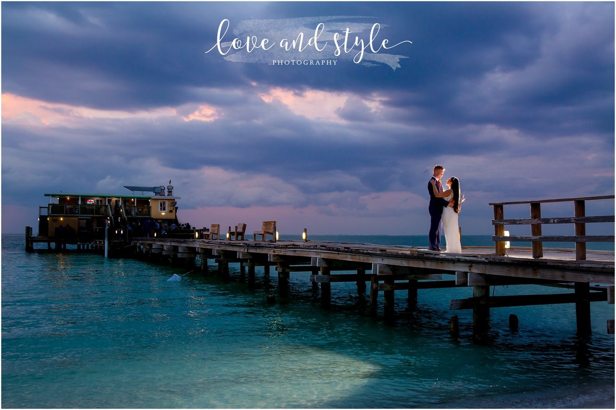 Rod and Reel Pier Wedding Photography of bride and groom with backlight at sunset