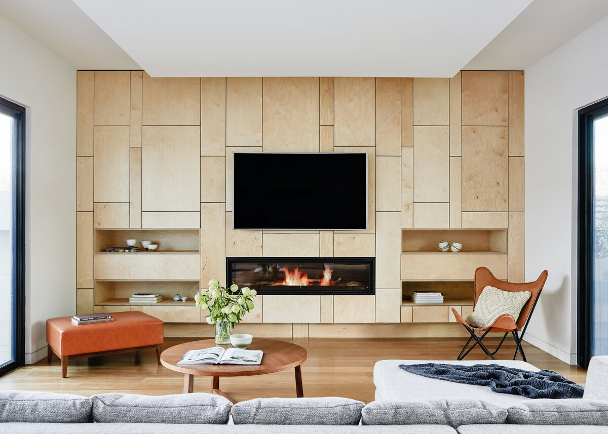 A flatscreen tv is hung on a wooden feature wall in a modern living room with a sleek fireplace inset.