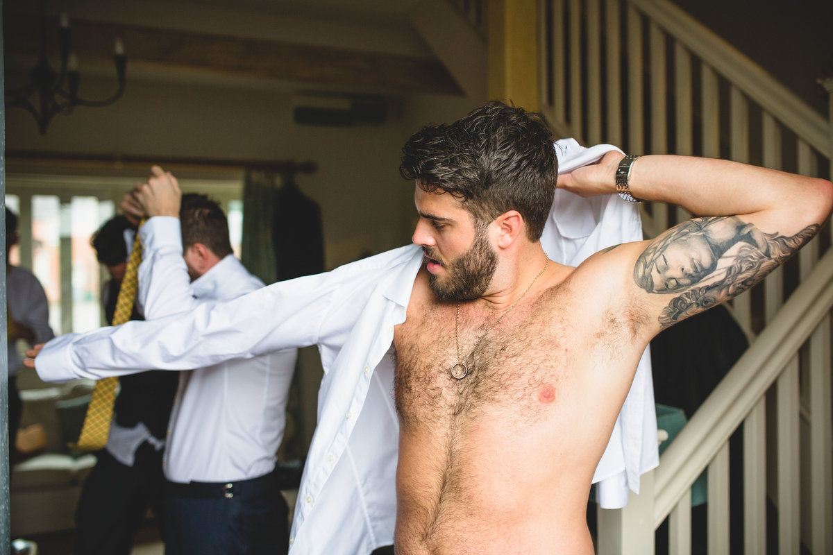 groom with tatoos getting shirt on