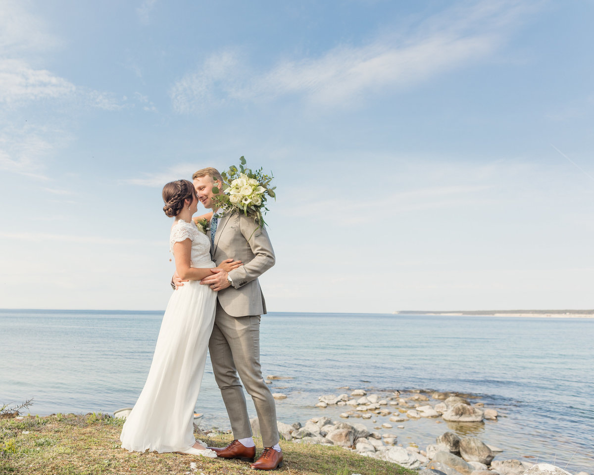 Wedding at Gotland with a weddingcouple hugging just by the shore and the horizon and open ocean and sky behind them.