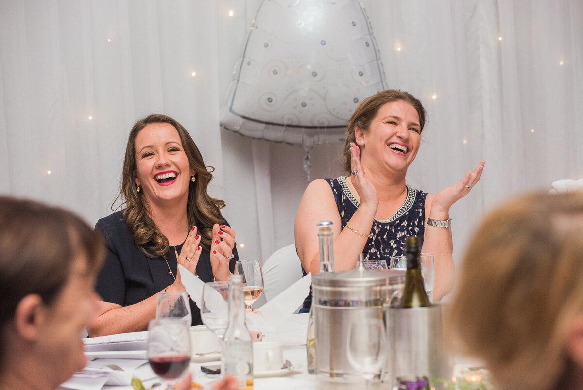 gay brides laughing and clapping at wedding reception