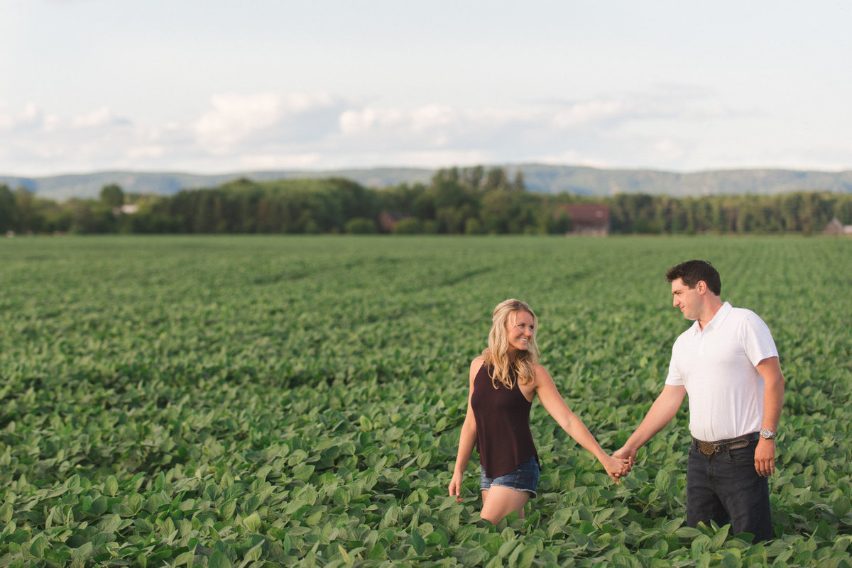engaged couple walking hand in hand in soybean fields