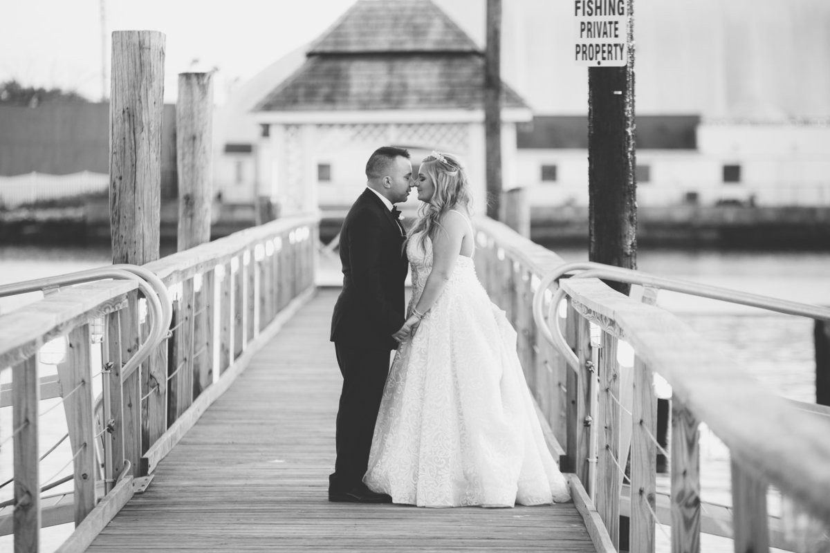 bride and groom kissing on boardwalk at Bridgeview Yacht Club