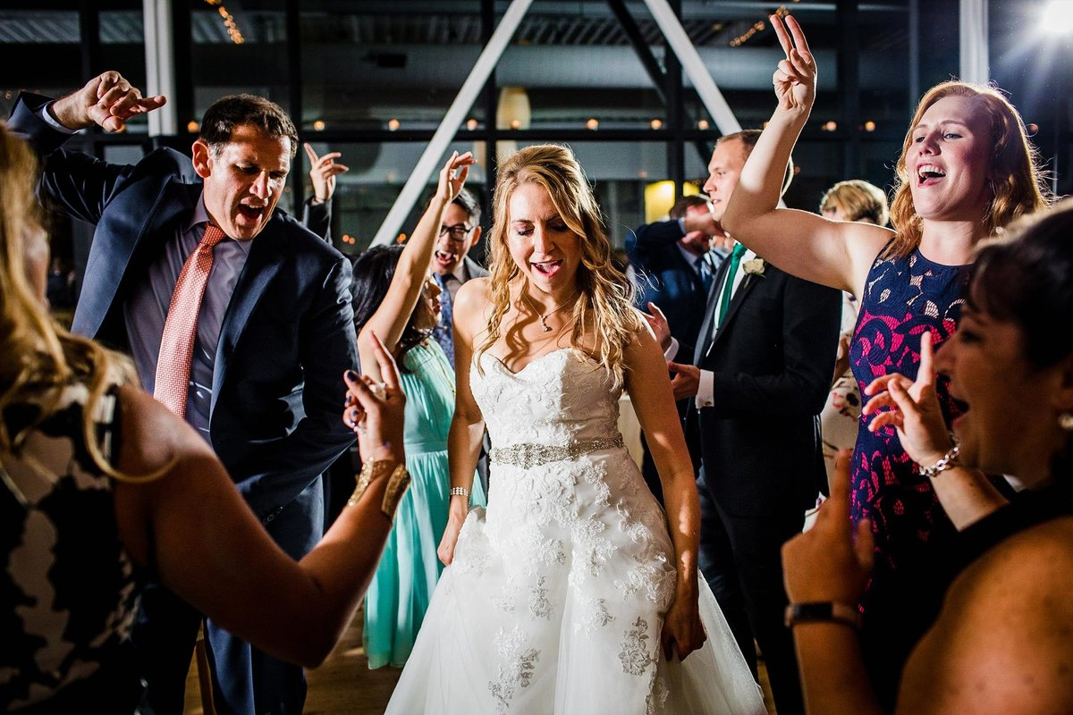A bride dances with guests at a Greenhouse Loft wedding reception.