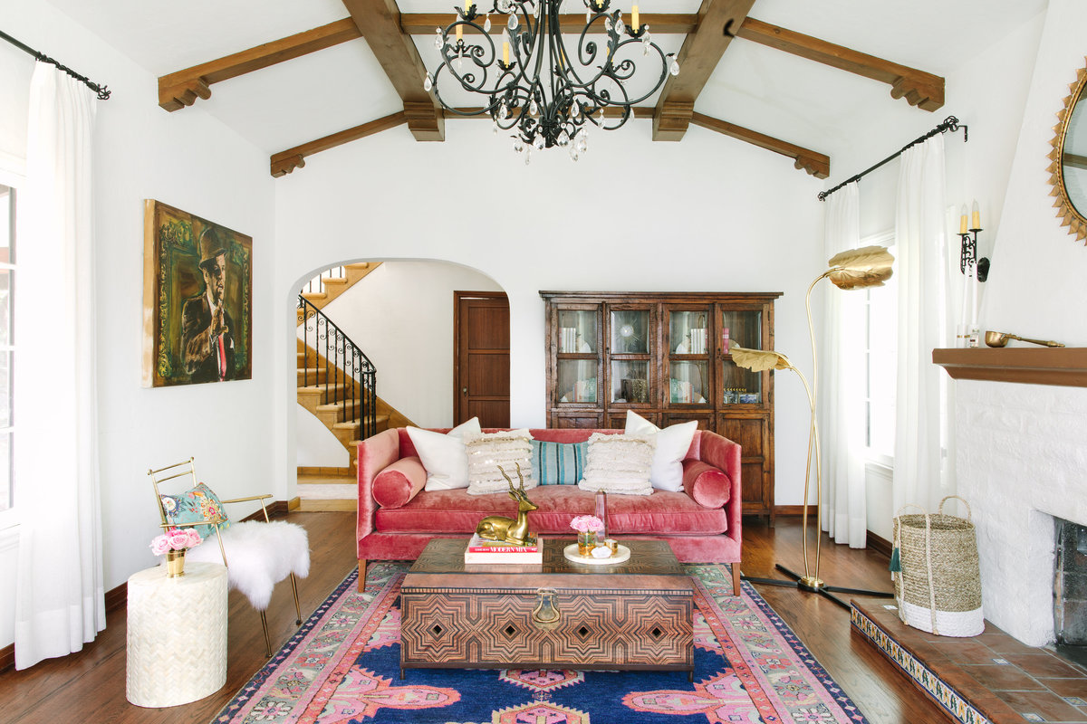 Colorful Spanish Revival living room with pink velvet sofa, Moroccan wood coffee table, Global Views Rimini floor lamp , and Caitlin Wilson Kismet rug