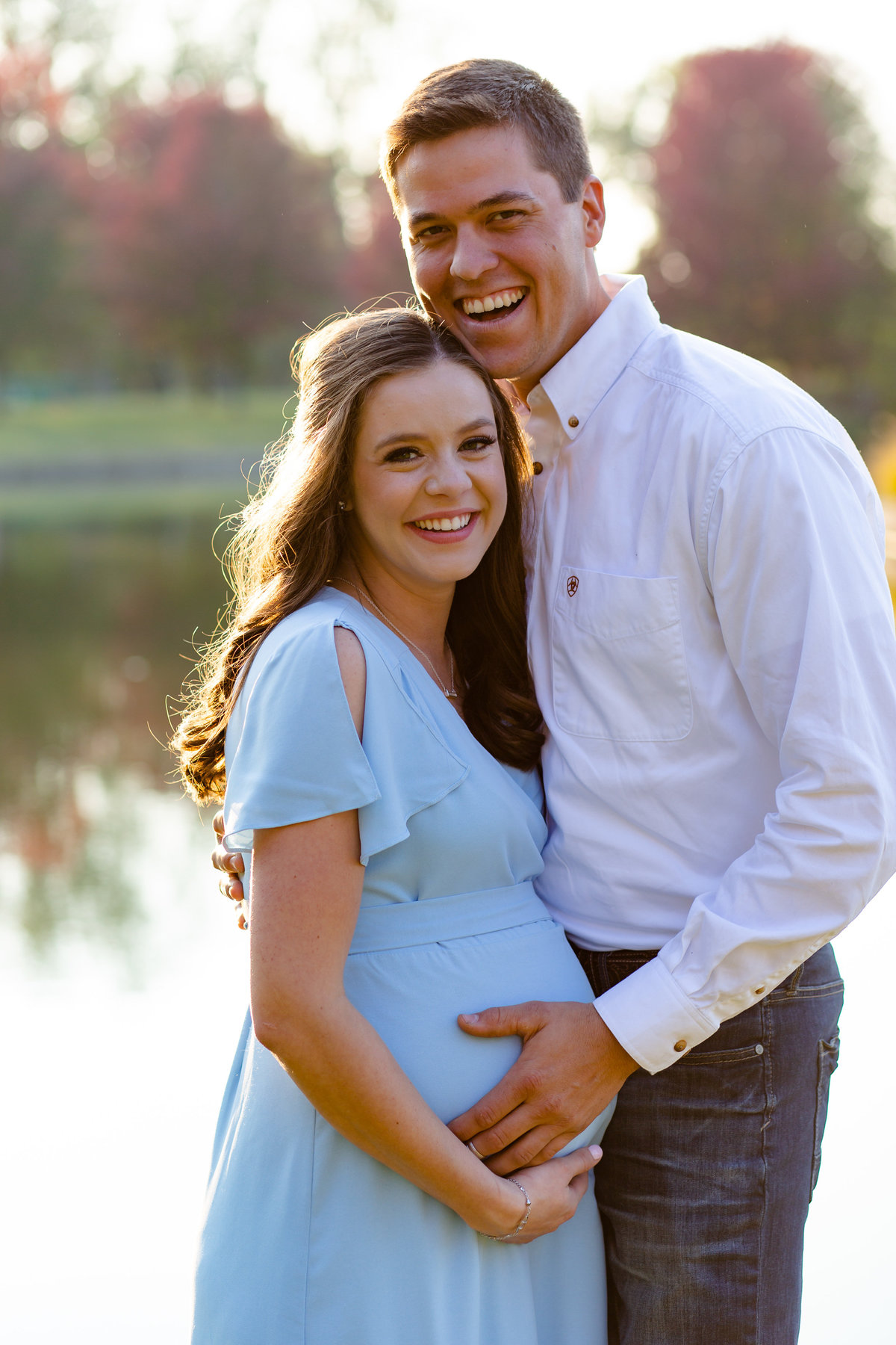 Fall Sunset Maternity Session with blue maxi dress standing by water with red trees  at Pagoda Circle in Forest Park in St. Louis by Amy Britton Photography Photographer  in St. Louis