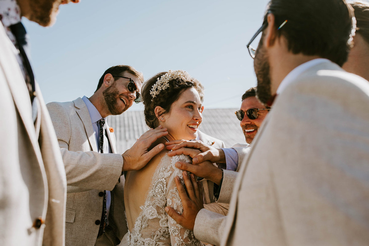 Groomsmen surround bride with hands on her shoulders.