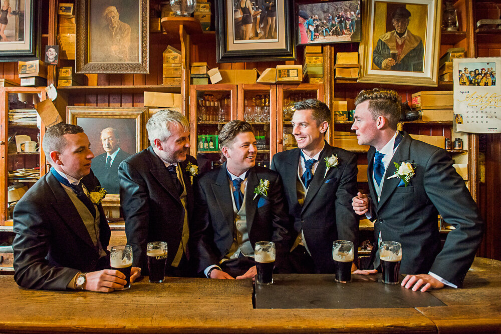 Groom and groomsmen sitting in traditional Irish pub, wearing morning suits and drinking Guinness