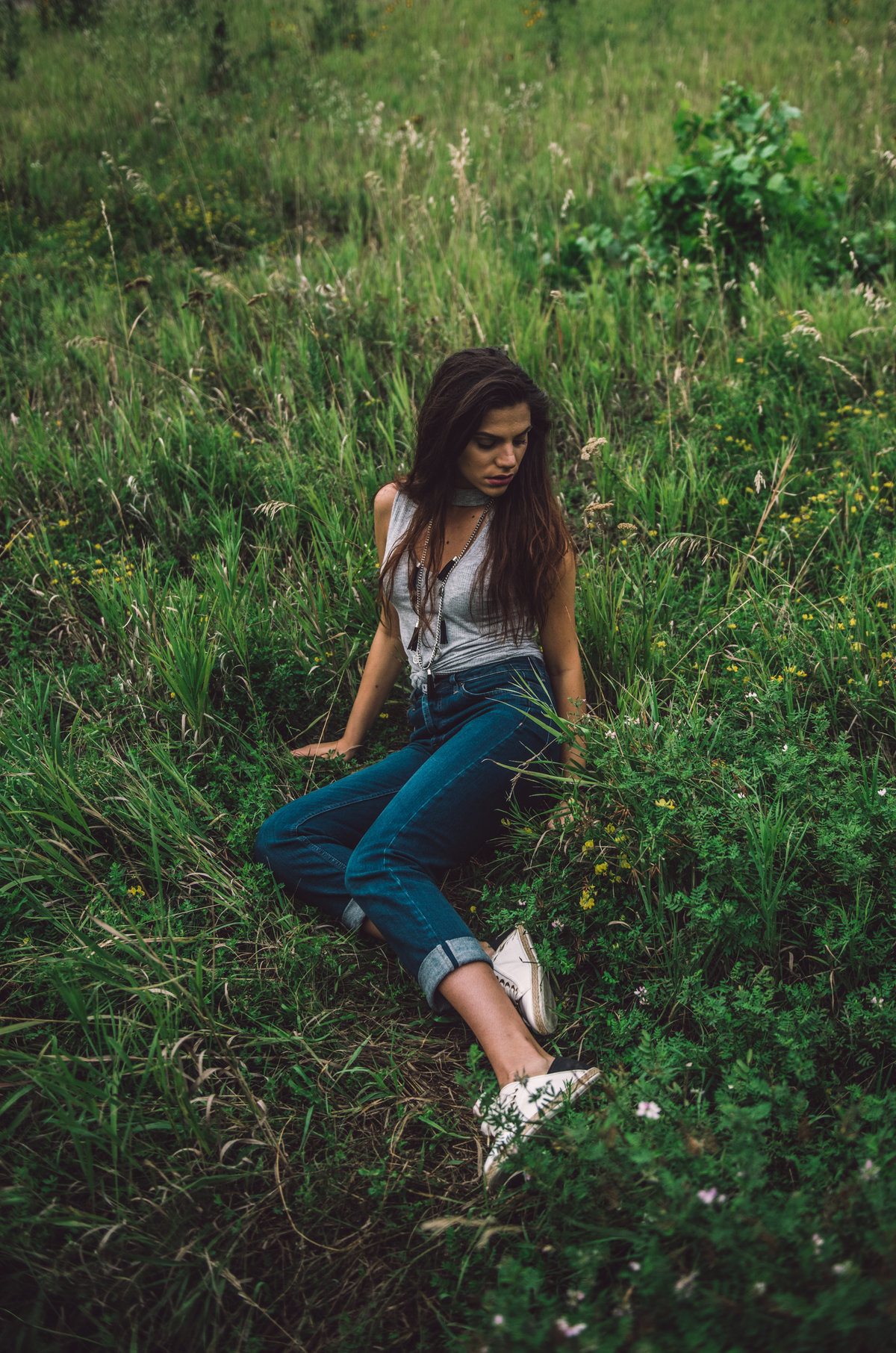 Gril n jeans sitting in grass