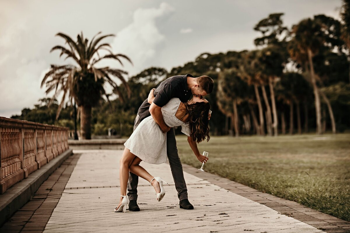 An image of an engaged couple marking their engagement in a beautiful park, holding their champagne glasses as the man dips his fiancee down and they romantically kiss by Garry & Stacy Photography Co - Tampa engagement photographers