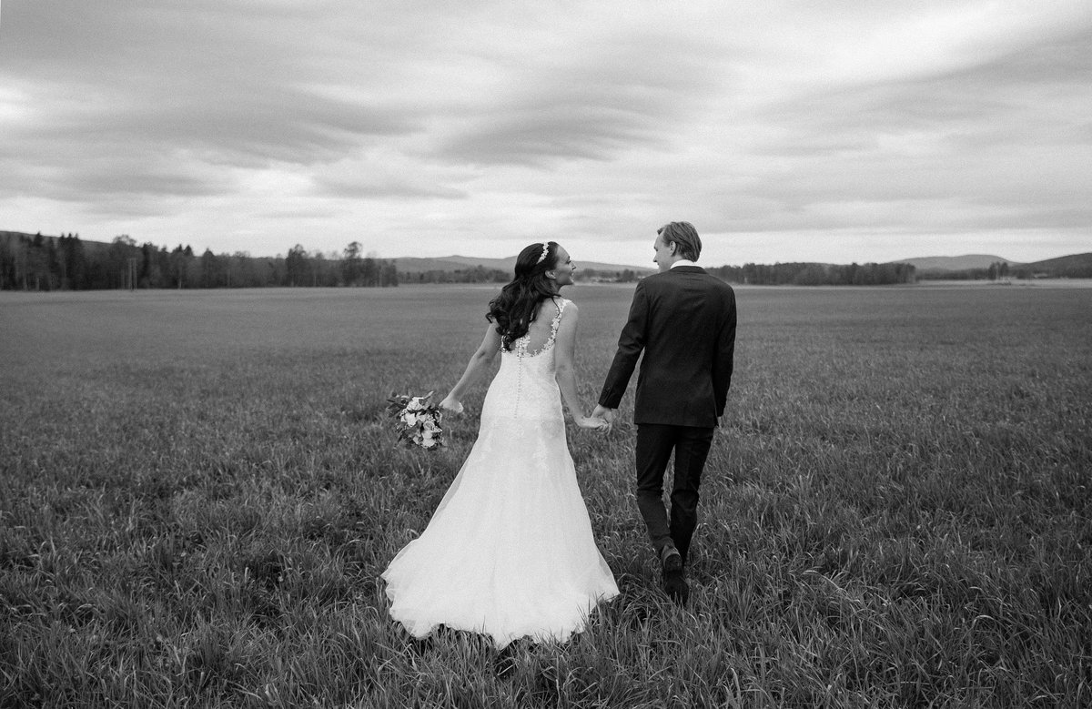 Just married couple holding hands walking through grassy field, hand in hand