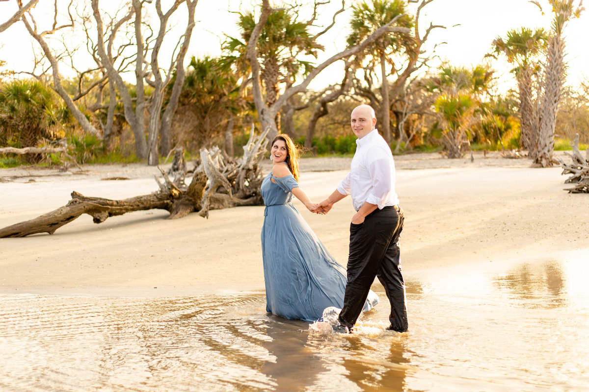 Couple walks through the ocean on the beach at the engagement session in Jekyll Island in Georgia