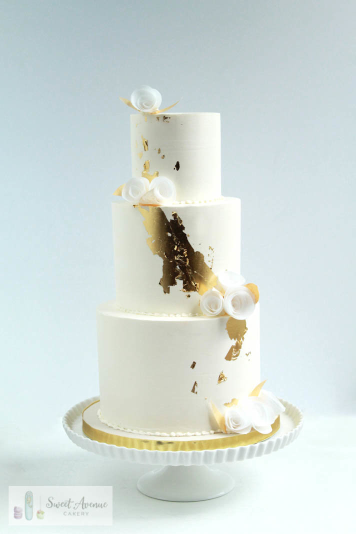 white and gold wedding cake with gold leaf and flowers