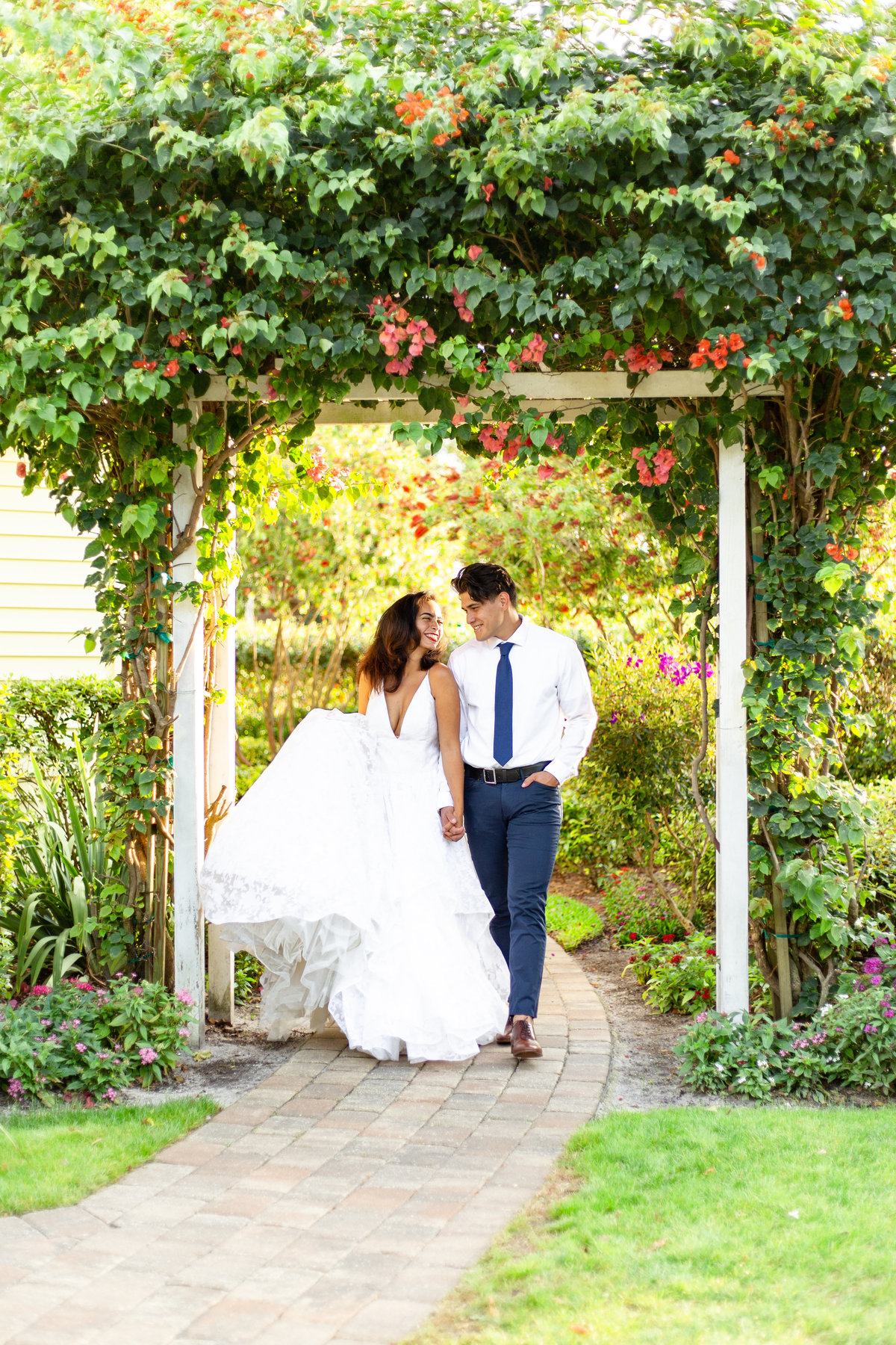 Bride and groom smile at each other as they walk hand in hand on their wedding day under an white arch in a garden wedding venue in Orlando, Florida