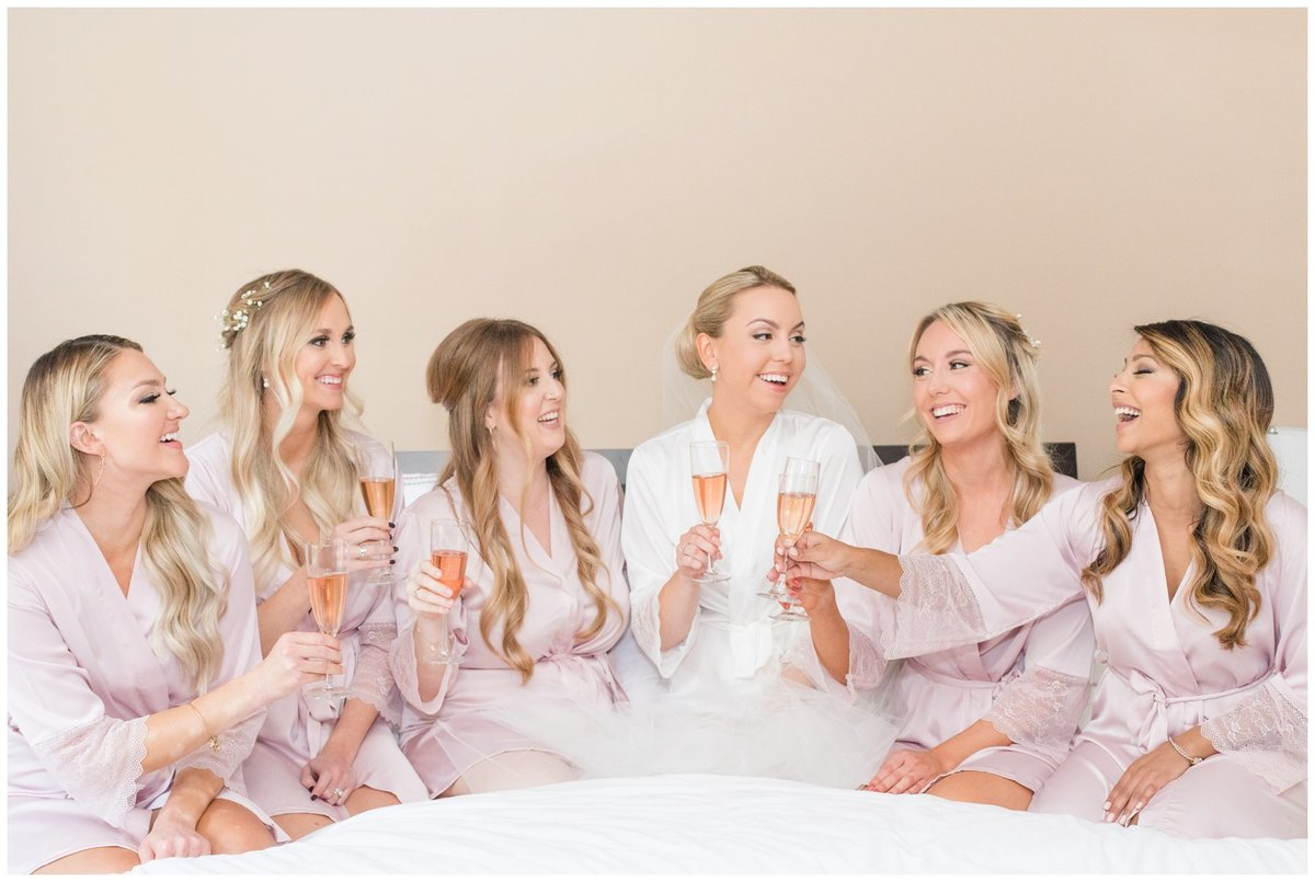 Light-and-Airy-Ottawa-Wedding-Photographer-bridesmaids-on-bed-champagne