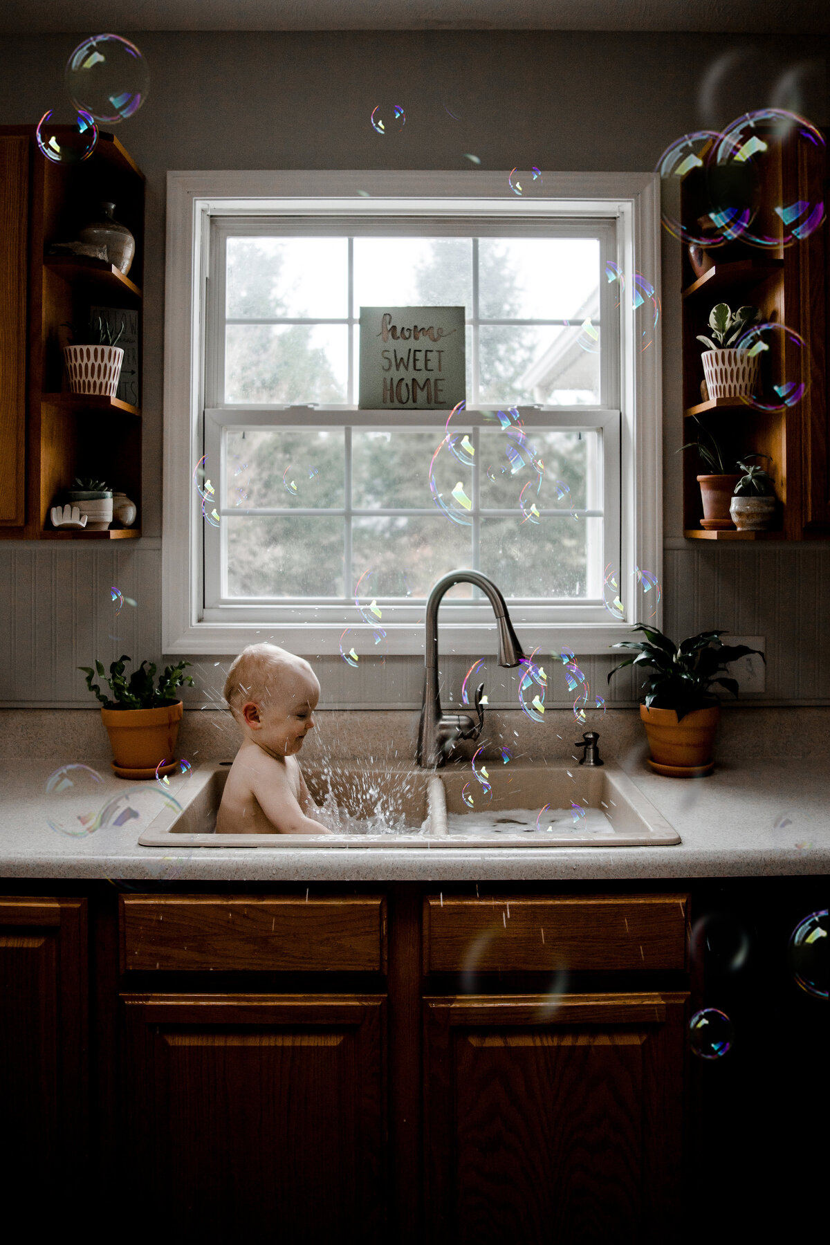 baby in sink with splashing and bubbles