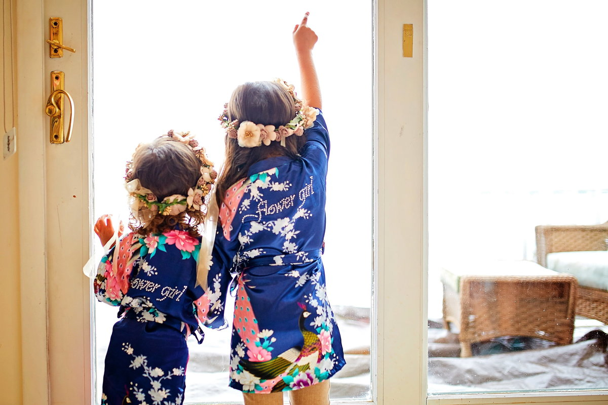 Flower girls looking out a window together in their flower girl robes