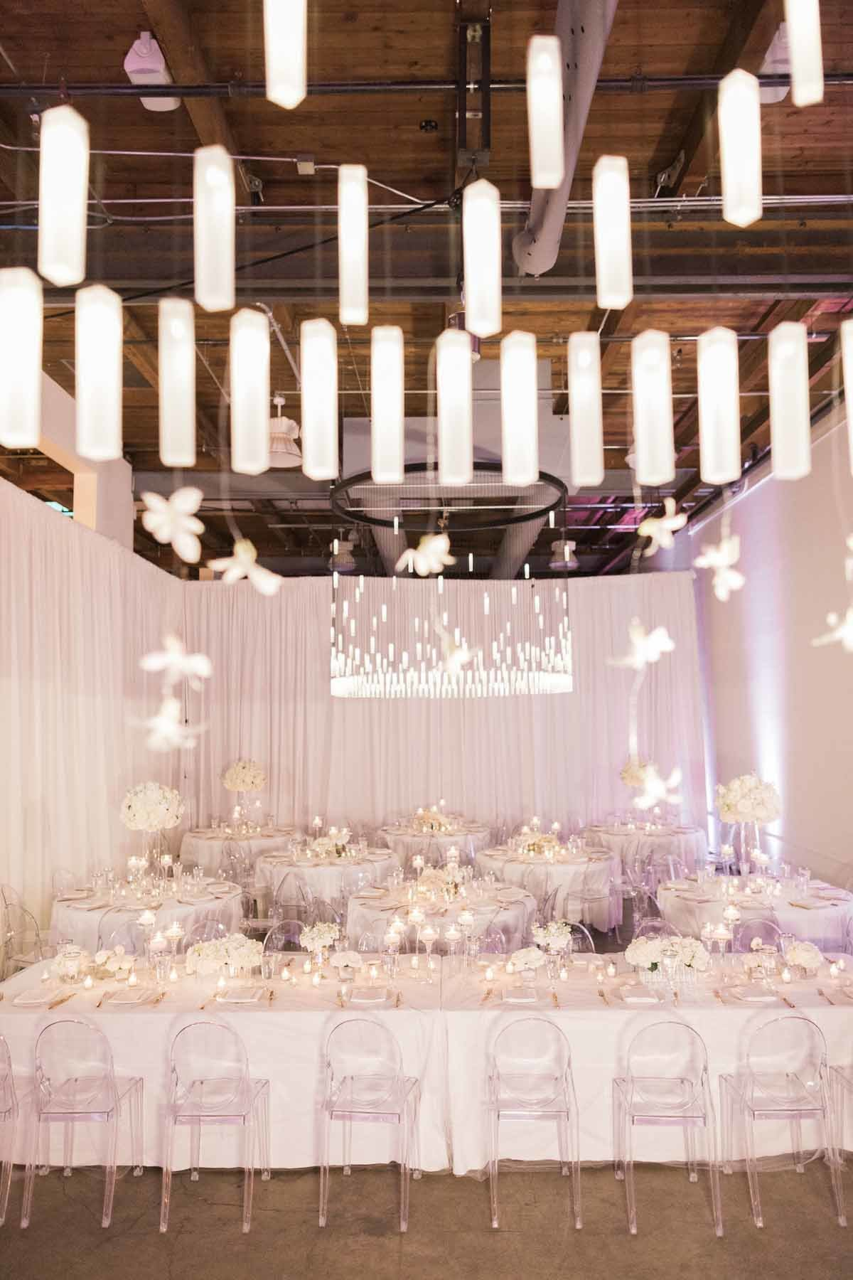 Chandelier with delicate white orchids hanging from it suspended over head table