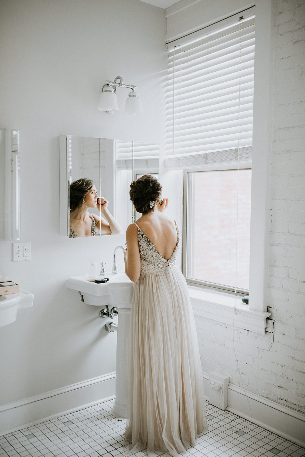 A woman looks out a window in front of a bathroom mirror.