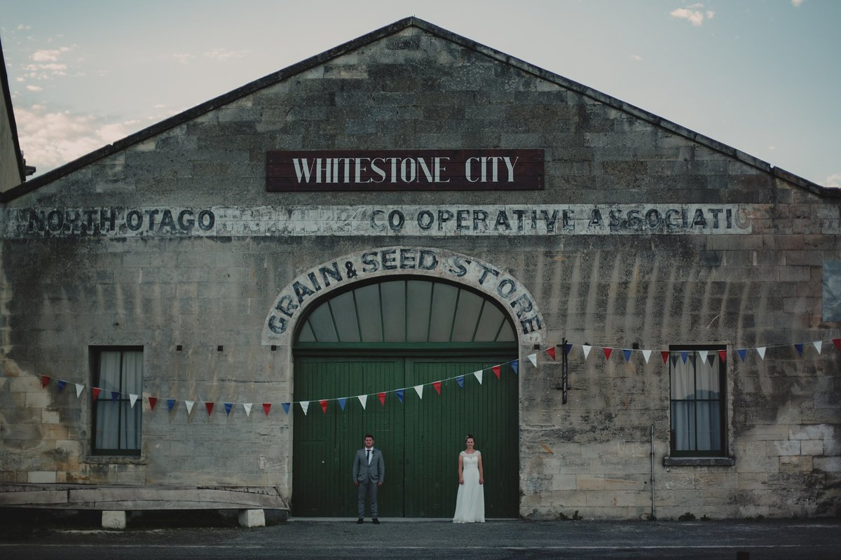 Bride and groom in front of Whitestone city building in Oamaru