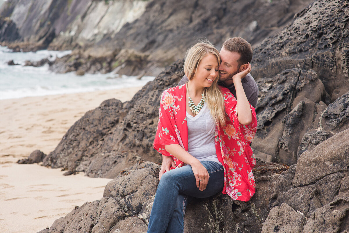 Young couple sitting on a rock on the beach embracing