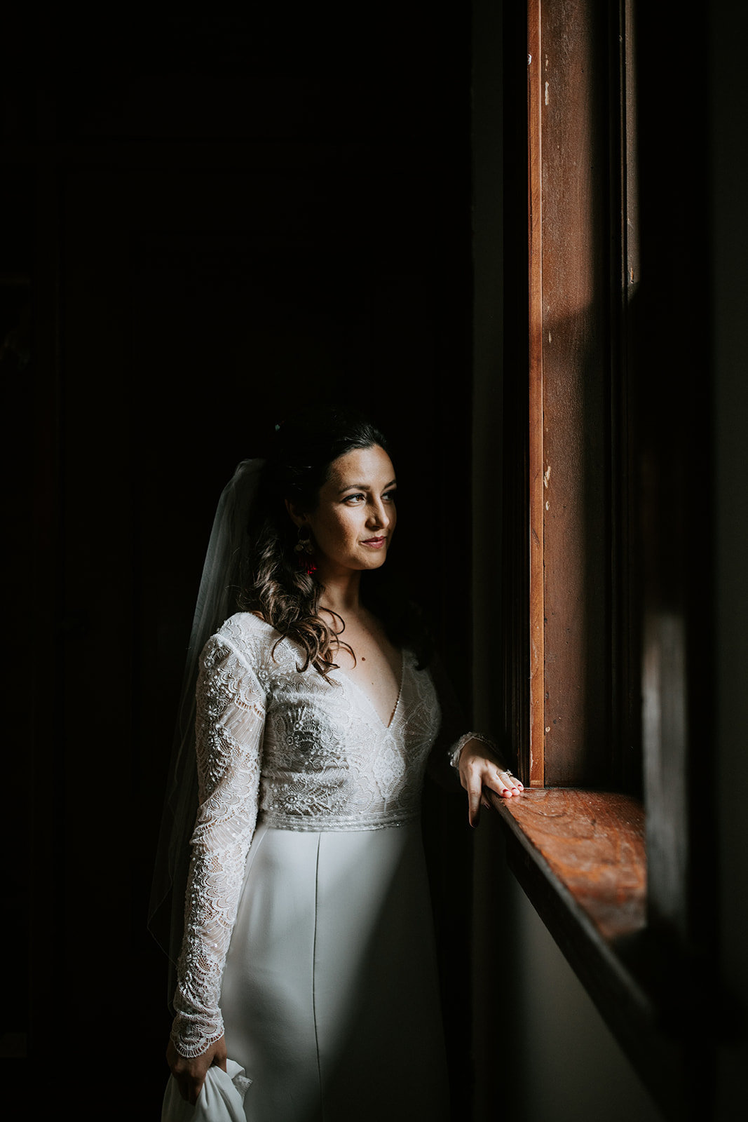 A bride looks out a window.