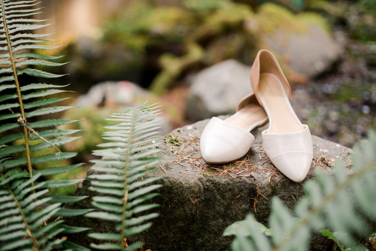 bridal slipon shoes on a rock among ferns