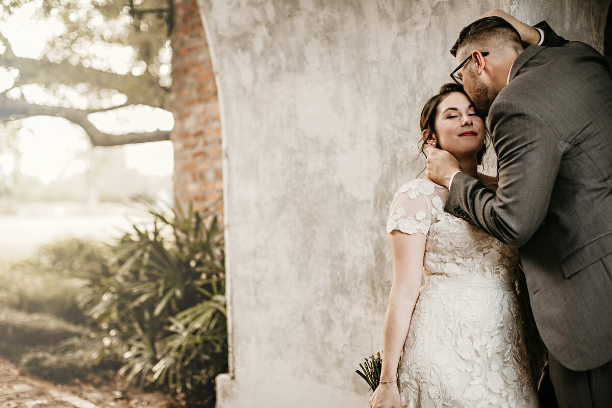 An image of the groom leaning over to tenderly kiss the bride's forehead and touch her neck as they stand in a vintage archway outdoors with plants in the background on their wedding day by Garry & Stacy Photography Co - Clearwater wedding photographers