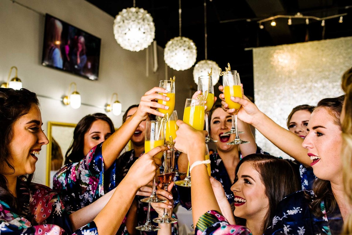 bridesmaids cheering with mimosas by stephane lemaire photography