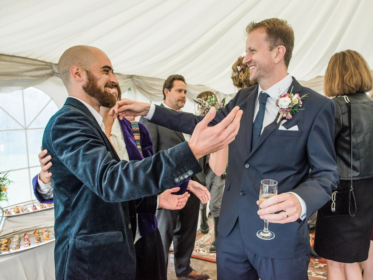 male guest in navy, velvet jacket embracing a groom in a navy wedding suit and wild flower buttonhole