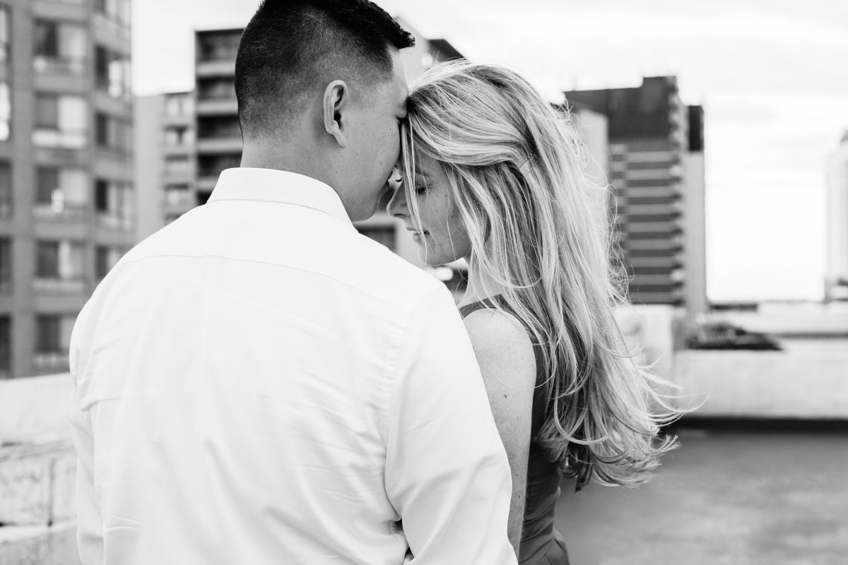 Guy-rests-his-head-on-his-fiances-forehead-as-they-close-their-eyes-and-enjoy-being-together-on-a-rooftop-in-windsor-ontario