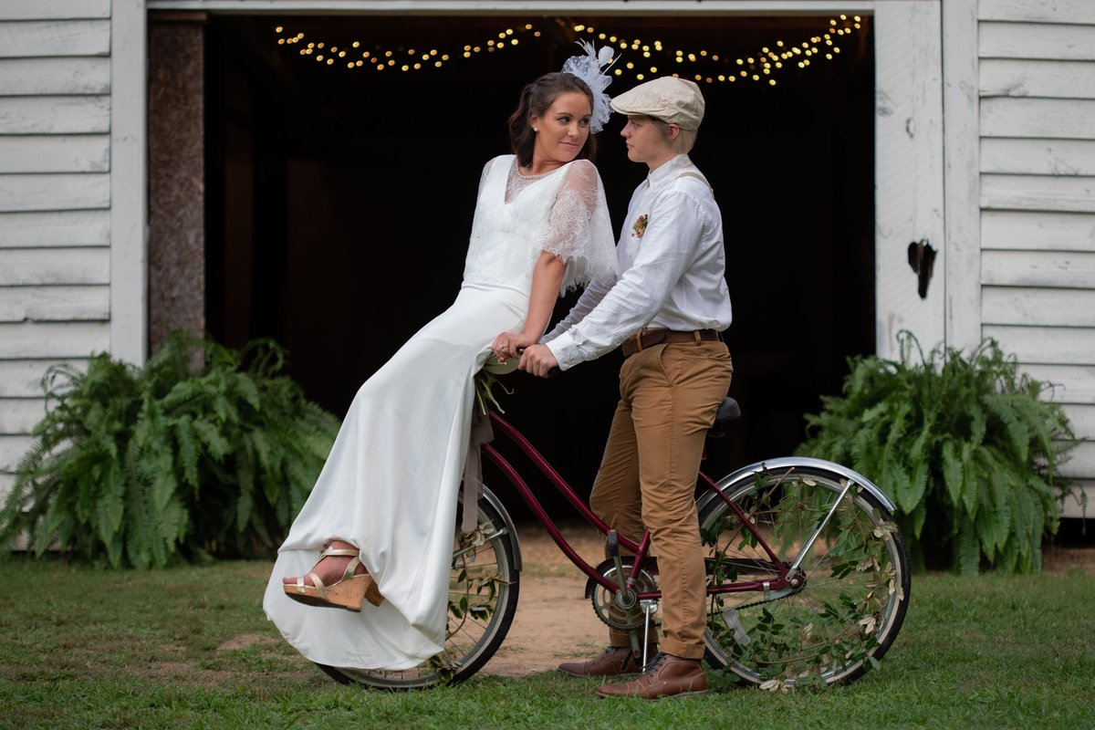 1940's styled wedding of bride and groom on vintage bicylce