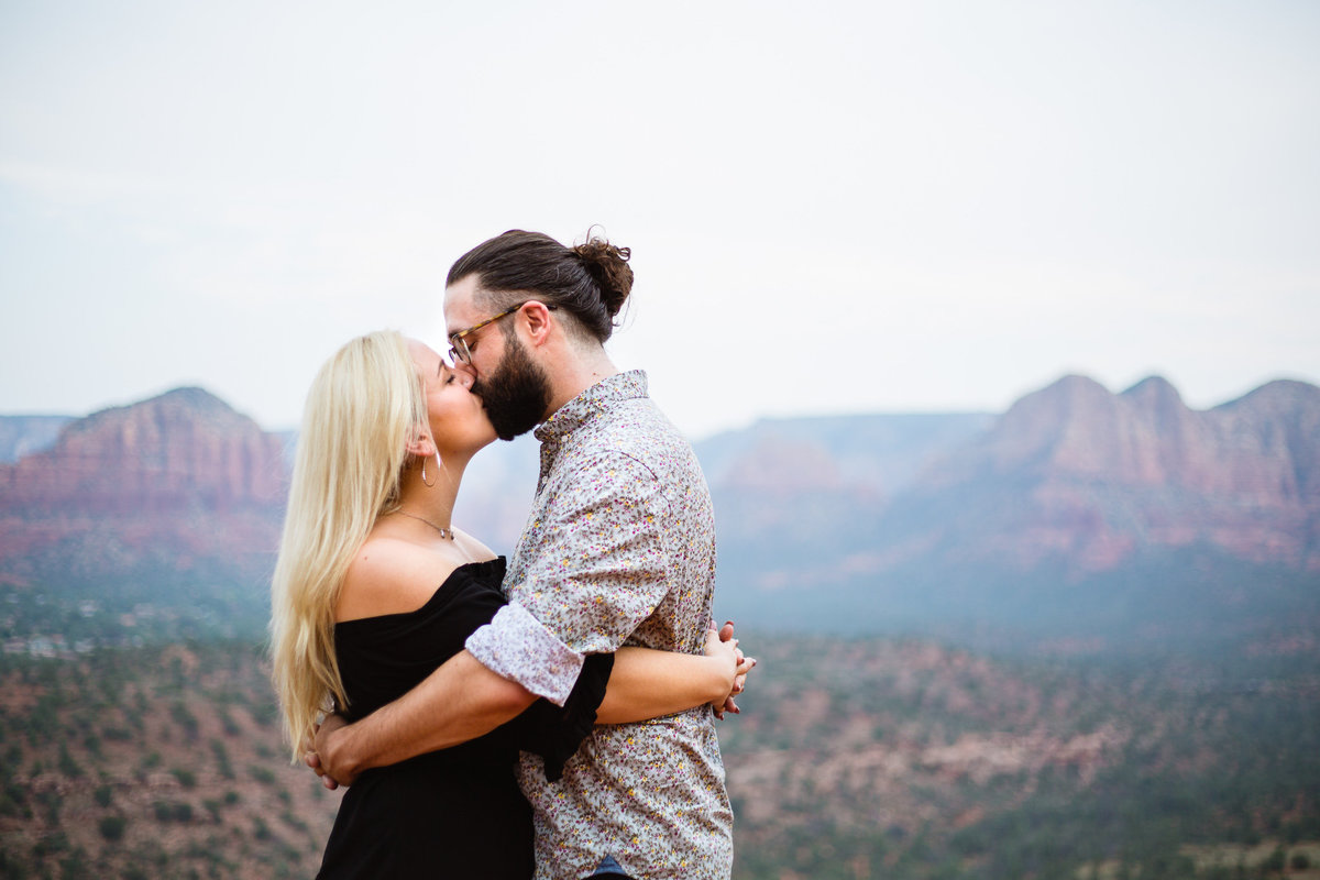 Couple kissing with epic views of Sedona during their adventure engagement session by PMA Photography.