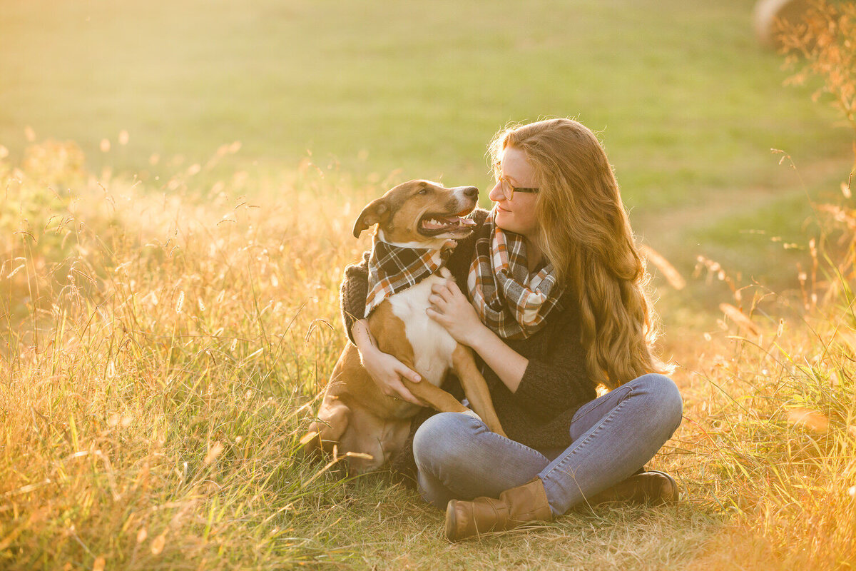 girl and pet dog in field at sunset