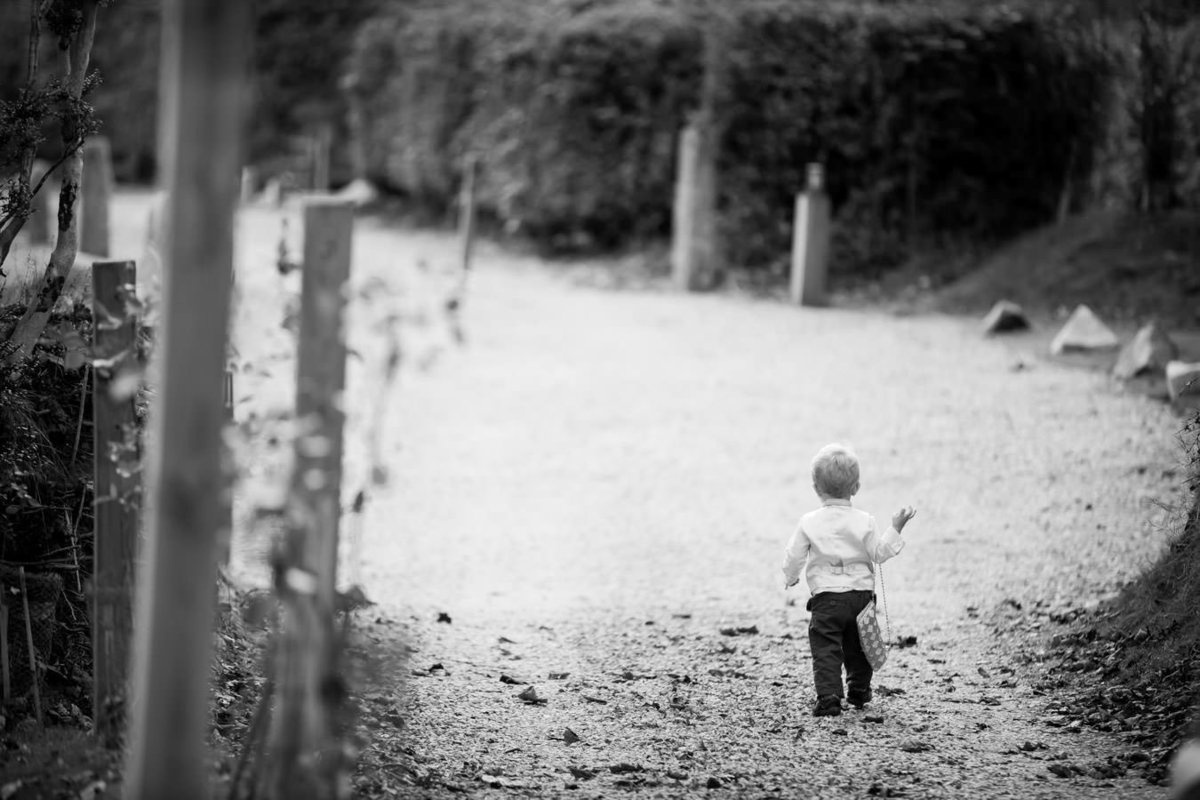 Cute page boy walking with handbag at The Green Weddings in Cornwall
