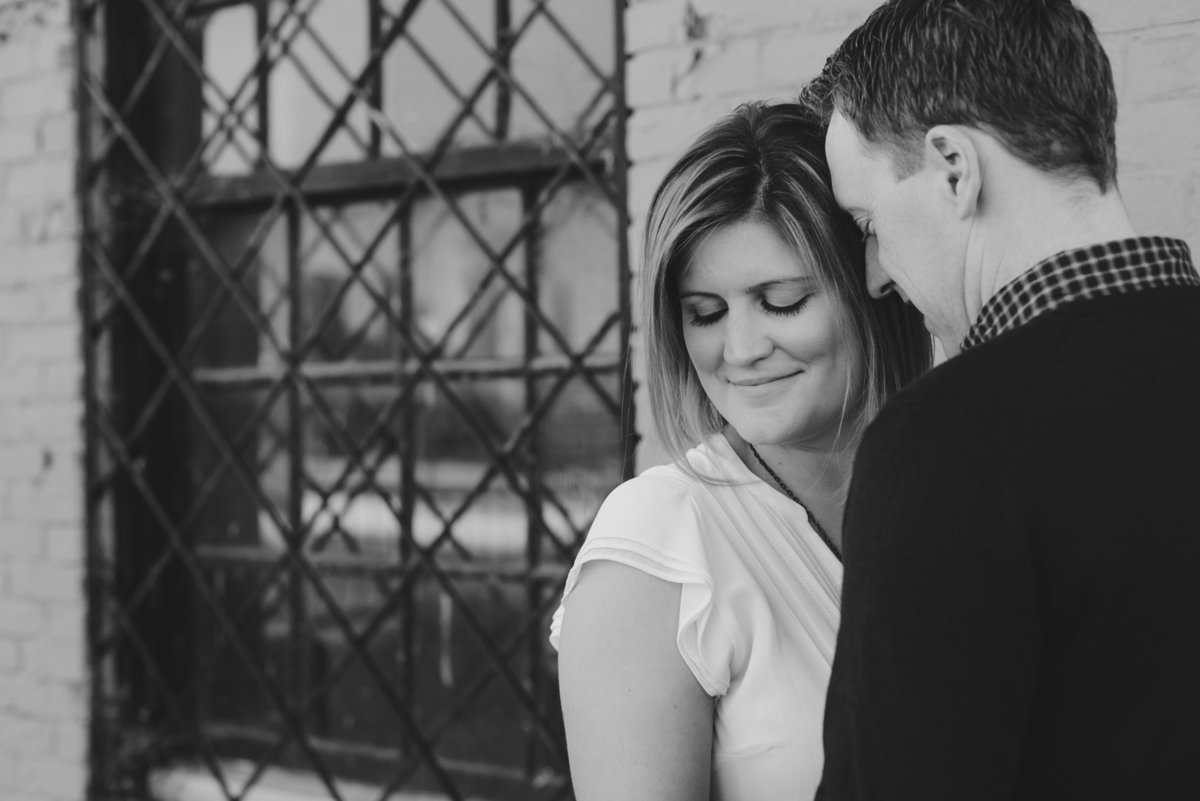 couple cuddling by an old rustic window in black and white