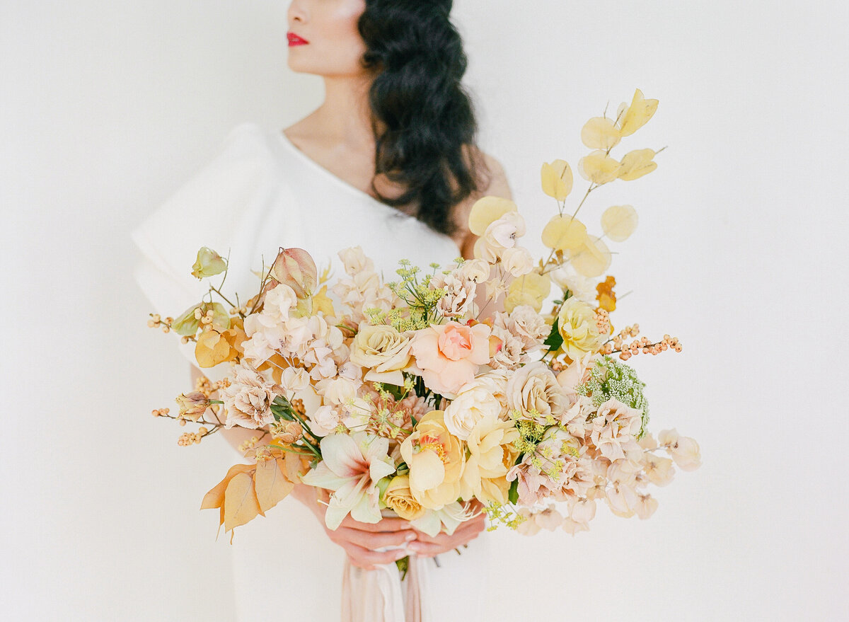 Bride holding a full, lush autumn inspired bouquet created by Le Bloomerie