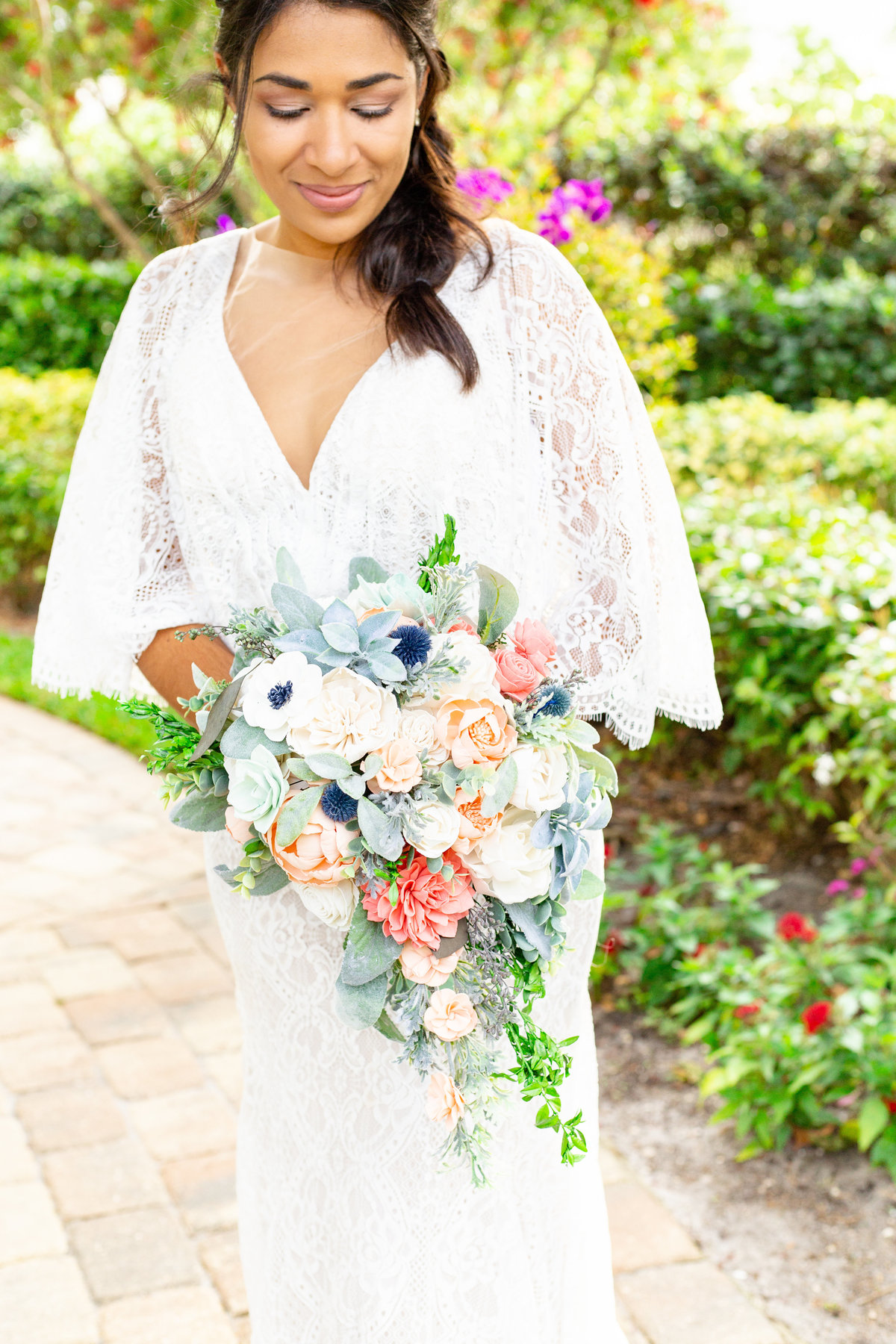 Bride holds cascading bridal bouquet made with bright wooden flowers in Orlando, Florida