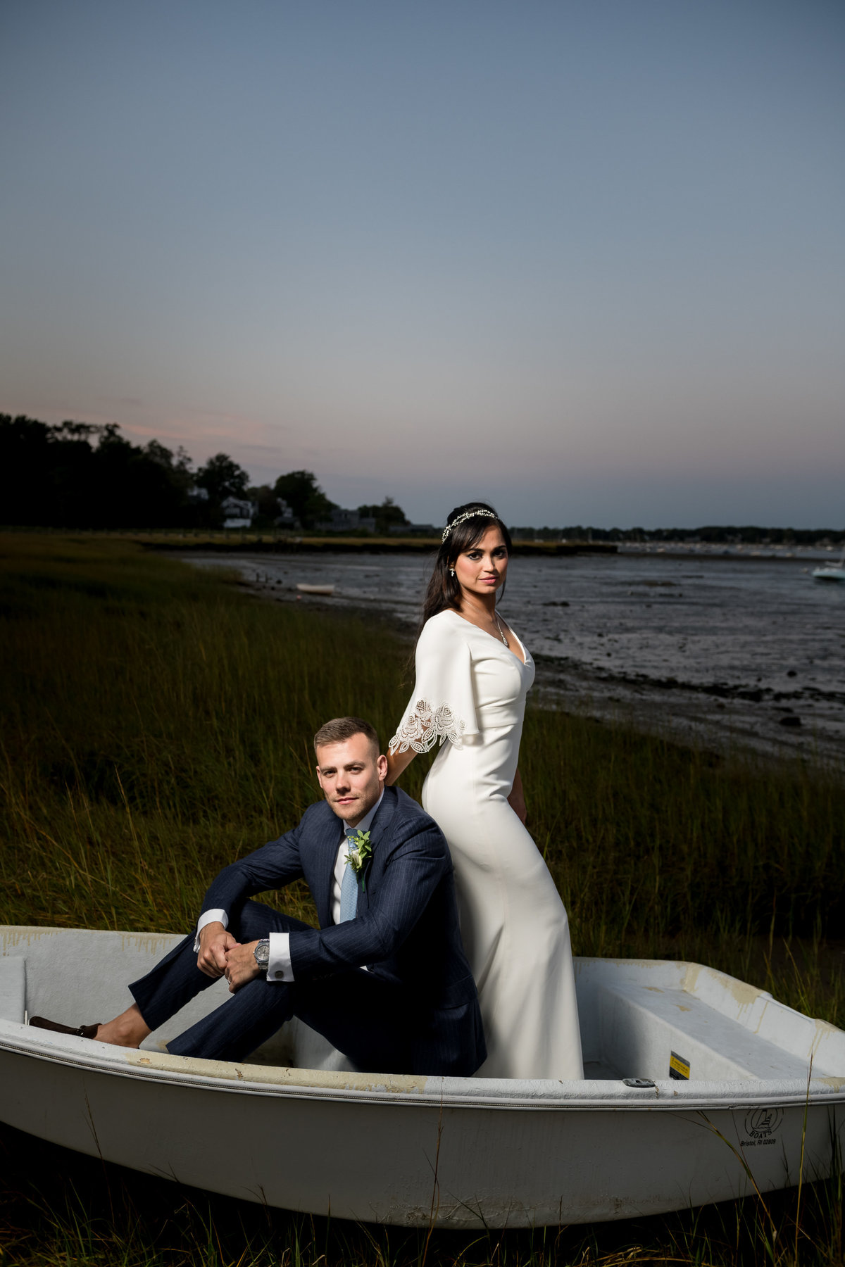 newlywed couple sitting in a boat by the beach after ceremnoy