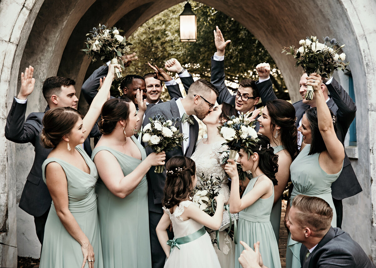 A picture of the bride and groom kissing, surrounded by their wedding party raising their arms and bouquets, cheering them on
