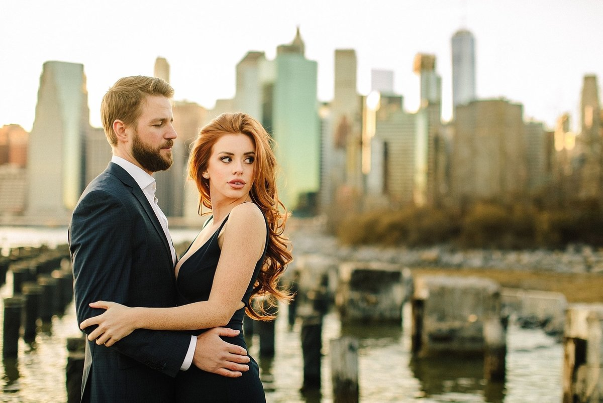 couple holding in front of downtown manhattan skyline