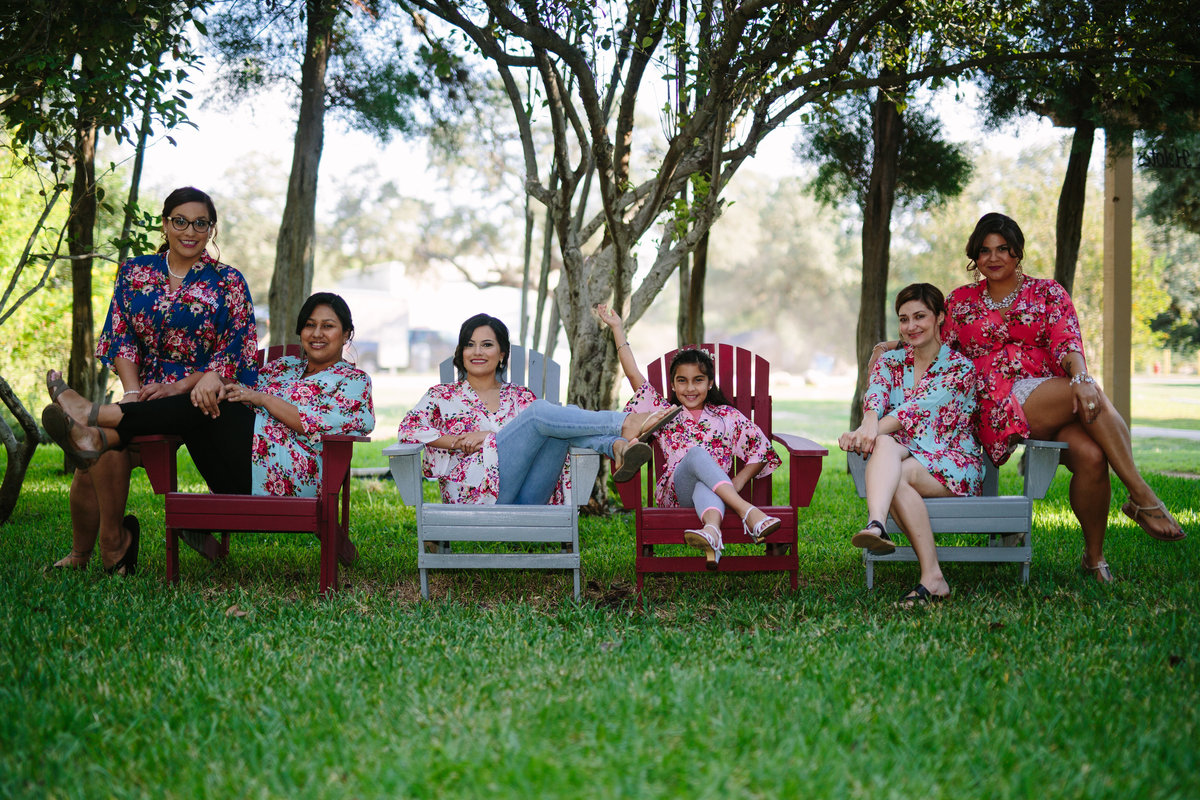 Bride and bridesmaids sitting outside in matching robes before wedding ceremony at The Gardens at old Town Helotes