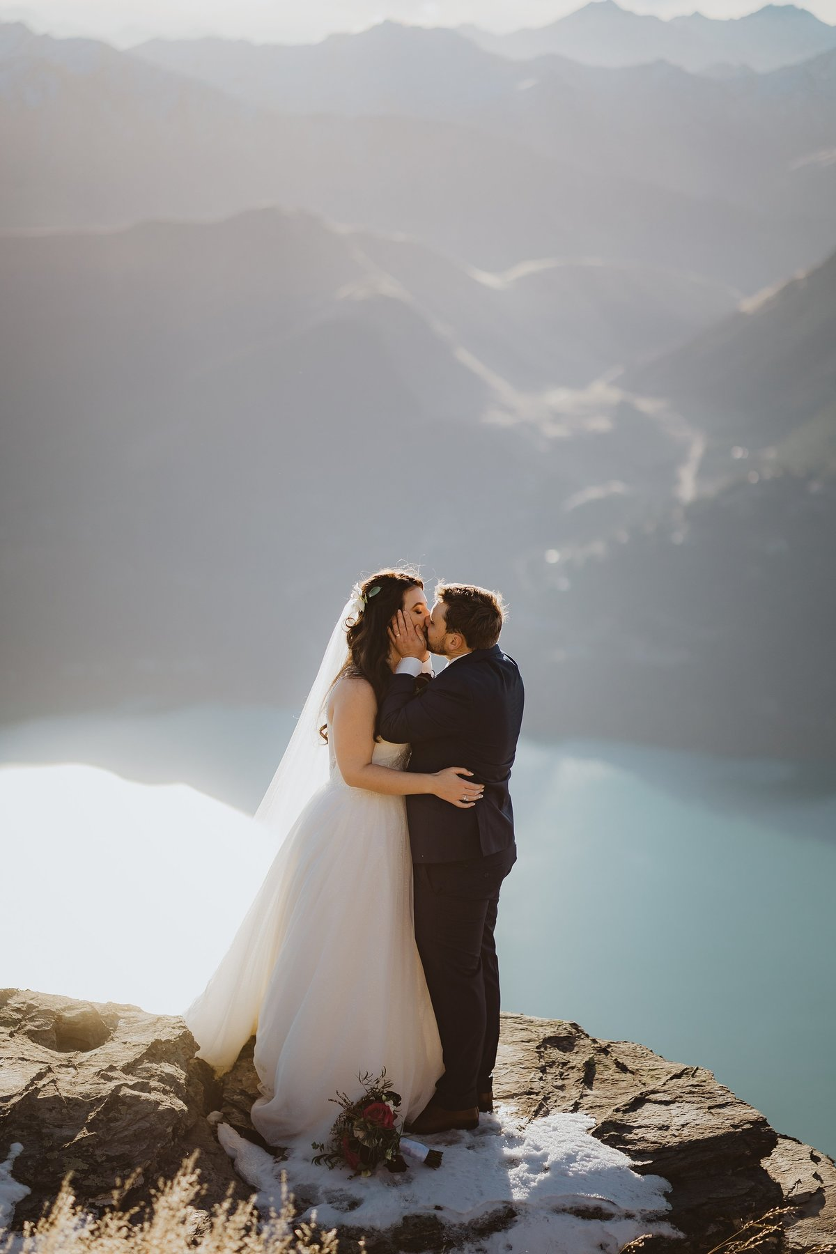 Groom grabbing his bride and kissing her on a cliff edge above a lake