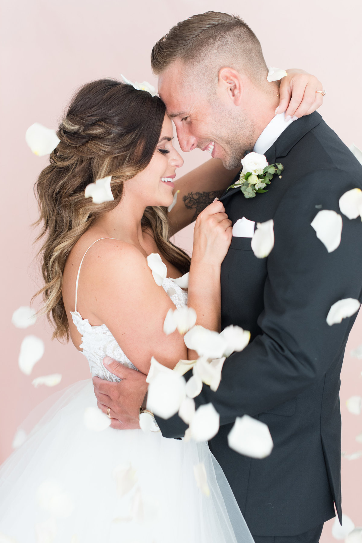 A bride and groom are showered with pink flower petals