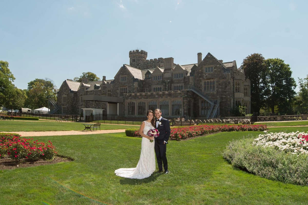 Bride and groom posing in front of Hempstead House