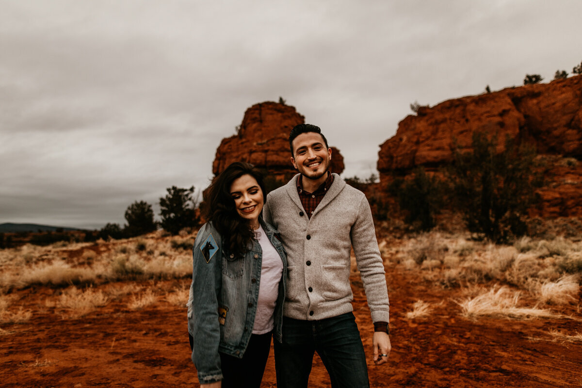 engaged couple walking in front of red rocks laughing
